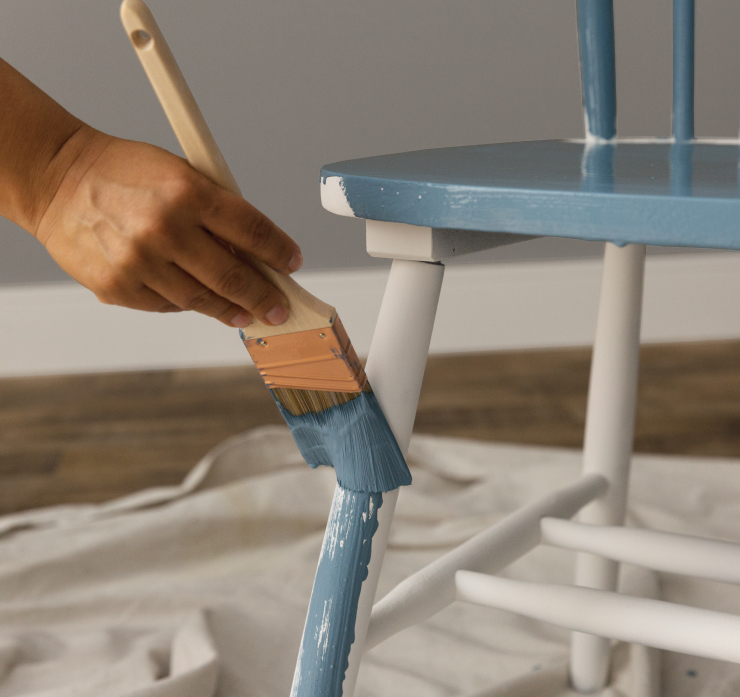 Chair legs getting a fresh coat of paint in a blue color called Blueprint.