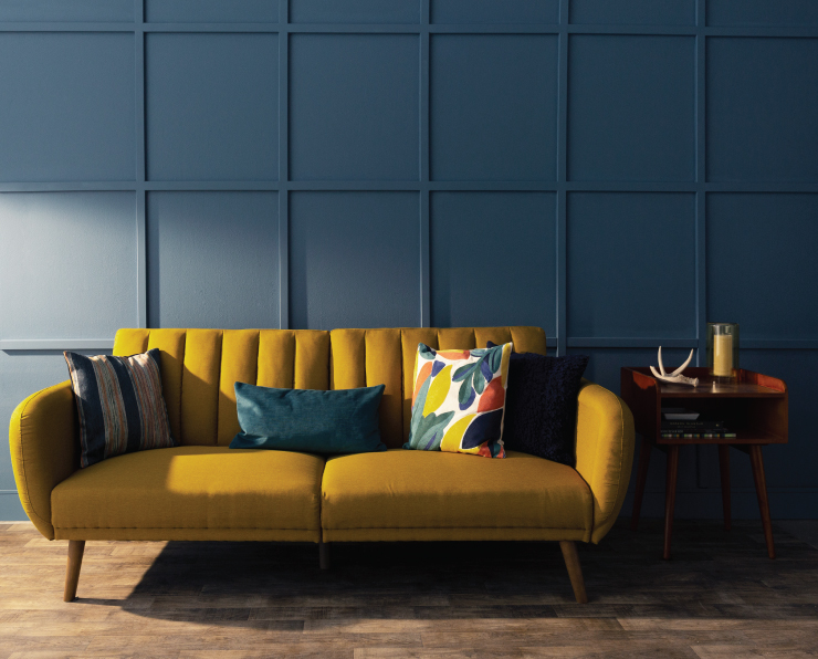 A living room with a yellow couch sitting in front of a wall that has square paneling and painted blue.