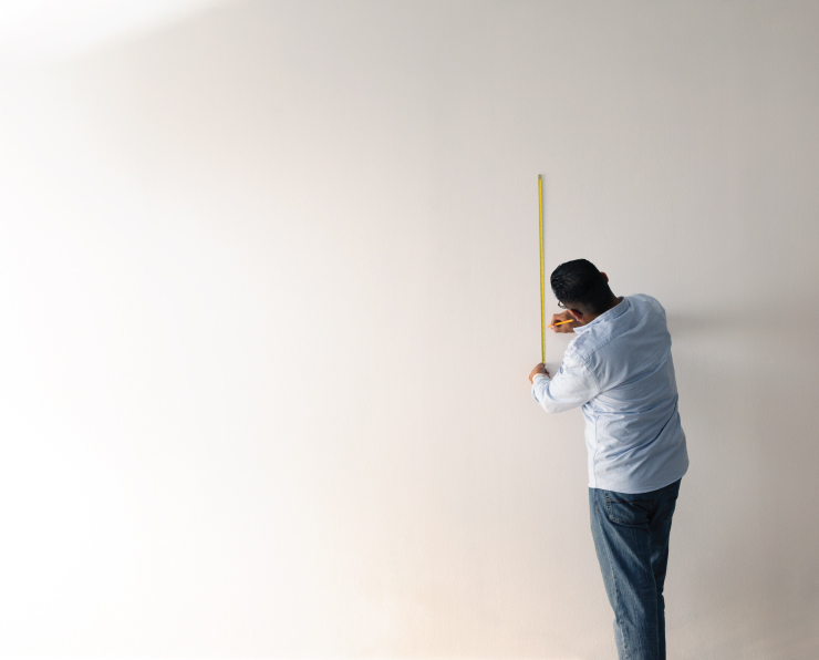 A person in front of a smooth, white wall marking of squares using a measuring tape and pencil.