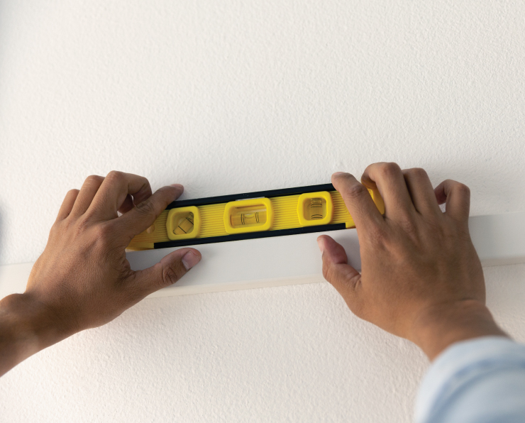 A person adding the wood to the smooth white wall. He is using a leveler tool to make sure the pieces are straight.