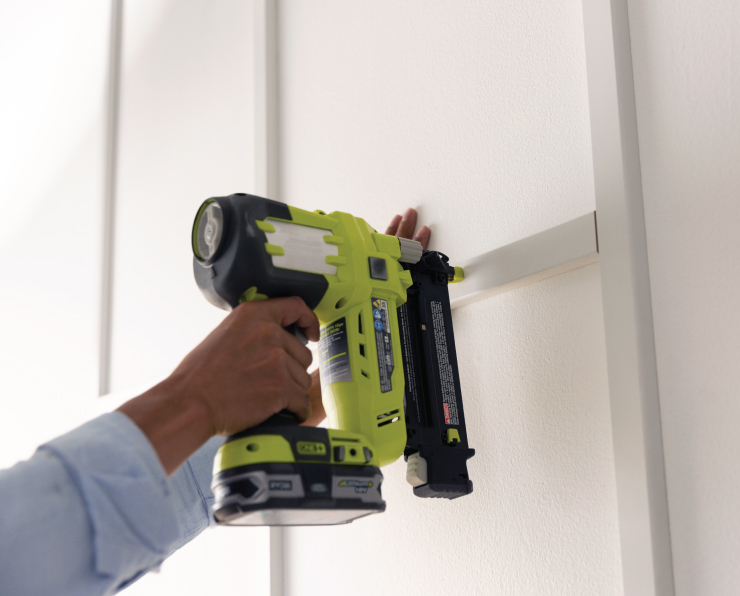 A person using a nail gun to adhere the trim pieces to the wall to form squares.