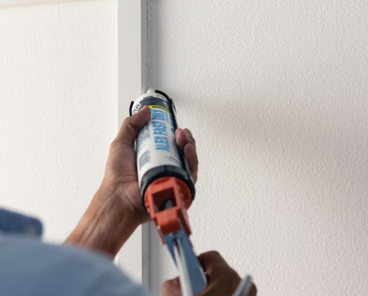 A person applying caulking to fill in the cracks.