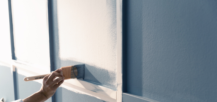 A person painting the white wall with trim in a blue paint color.