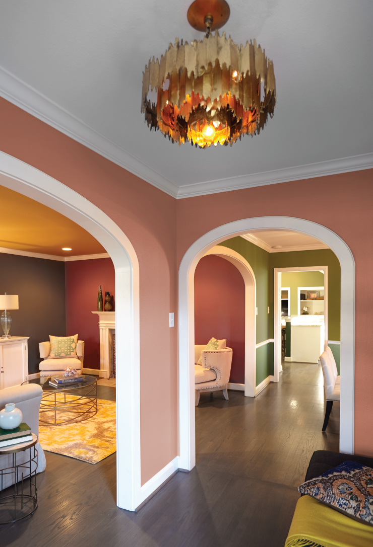 An interior of a home showing arch ways and views into other rooms. The walls are painted in multiple colors, yellow, green and red. Ceiling and trim are white.
