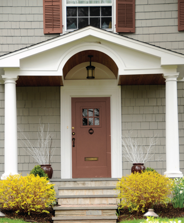 An exterior home painted in a gray color with the door and shutters painted in Mars Red.