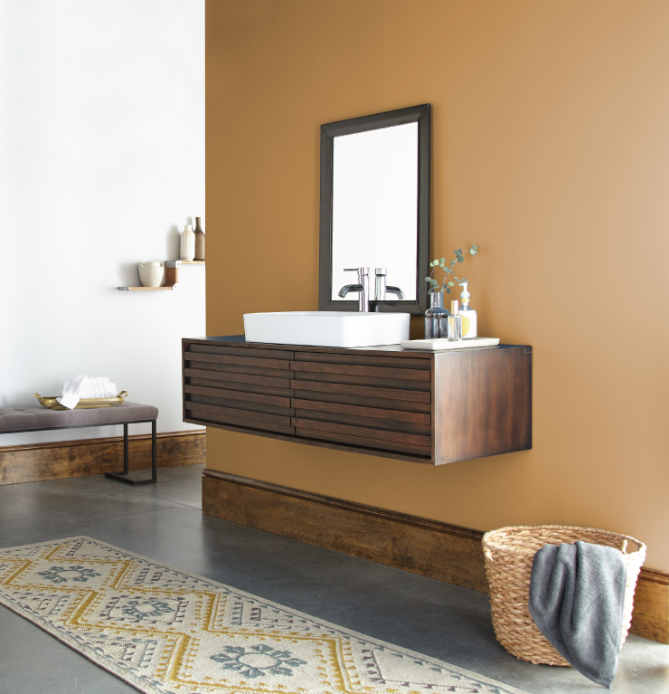 A bathroom with a dark wood sink. Wall is painted in Amber Autumn.