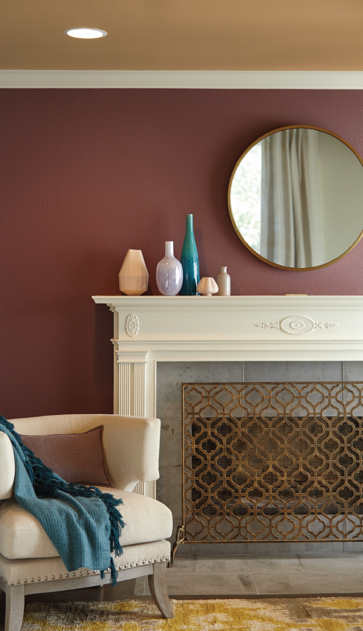 A close up view of a living room showing the fireplace and a chair. The wall is painted in a red color and the ceiling is painted in Amber Autumn.