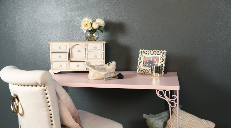 An image of a bedroom corner with a desk and chair. The jewelry box is sitting on the desk with a vase of flowers a makeup bag and a picture frame.