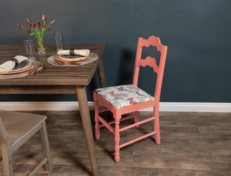 A dining area featuring wood furniture and an accent chair painted with a salmon coral color.
