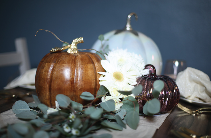 A cropped image of the table's centerpiece with pumpkins and green vines.