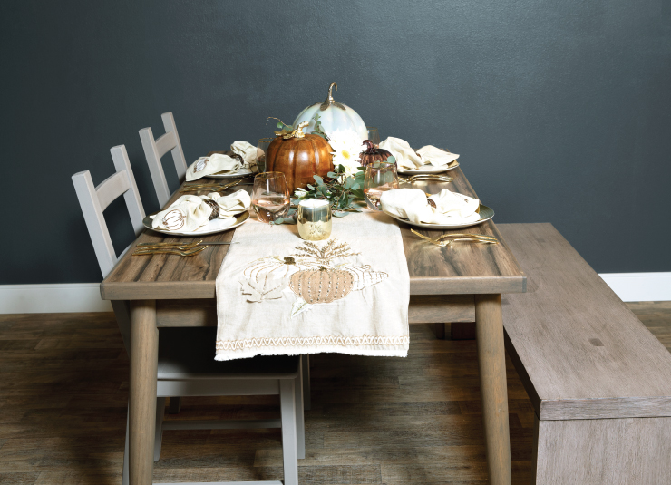 A dinner table set for four. The table is dressed in a cream runner and fall pumpkins at the end. Centerpiece is pumpkins, greenery, and candles. Table is wood with a bench on one side and two chairs on the other. The wall behind the table is painted in a dark grayish-blue color.