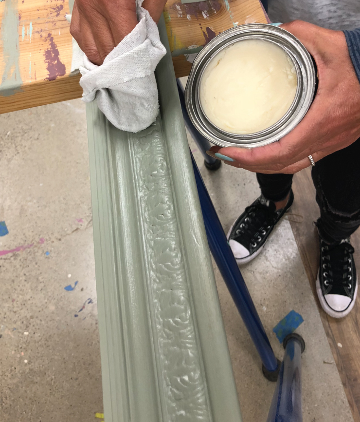 A person using a rag to apply Behr's decorative clear wax to the painted frame.