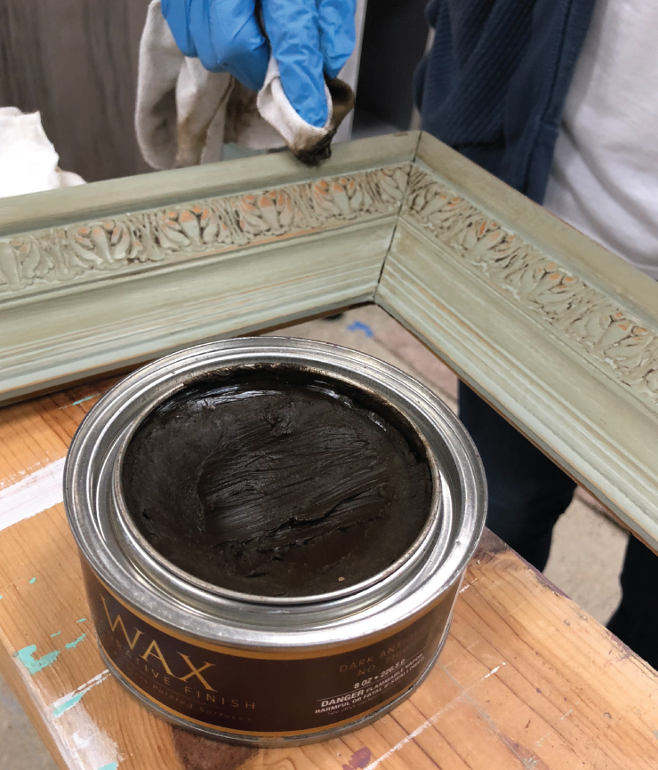 A person using a rag to apply Behr's decorative dark wax to the painted frame.