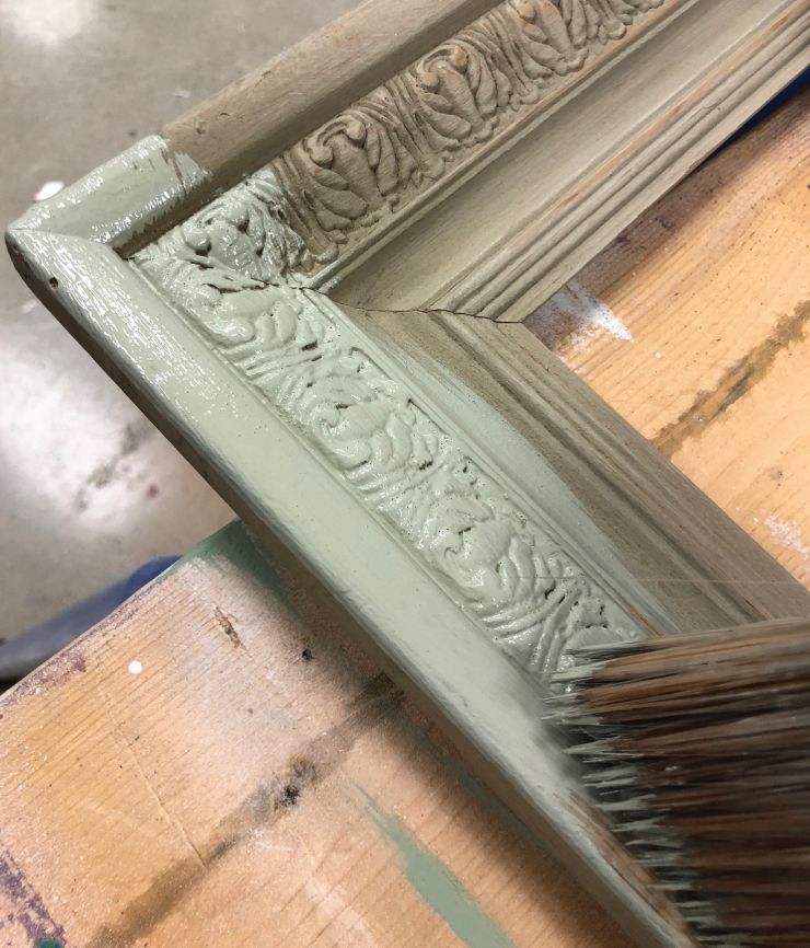 A person using a paint brush to apply Behr's decorative chalk paint in a light green color.