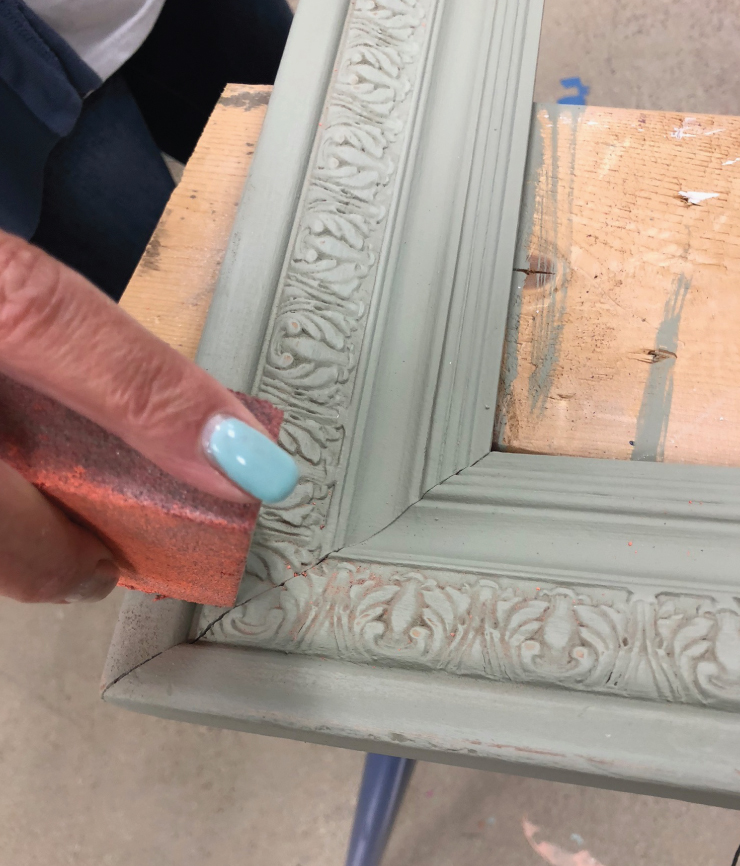 A corner of the painted picture frame. A person is sanding the painted frame using a sanding block.
