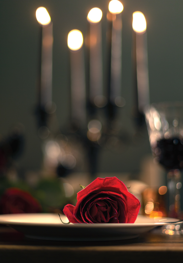 A tight crop of one plate setting with the rose on the plate. The rose is in focus, the background are the blurred candles.