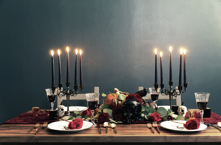 The same table now set for a romantic dinner with tall candles added, wine glasses and roses on the plates.