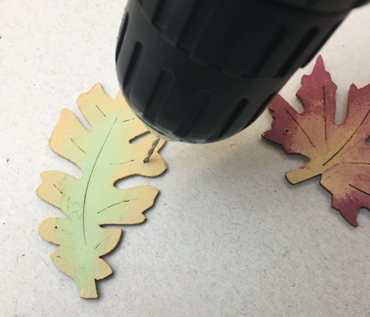 A person drilling small holes into the painted wood leaves.