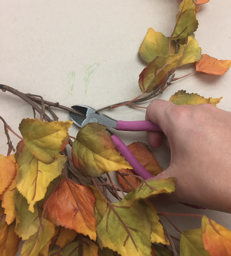 Person with wire cutters cutting leaves from a plastic fall leaf vine.