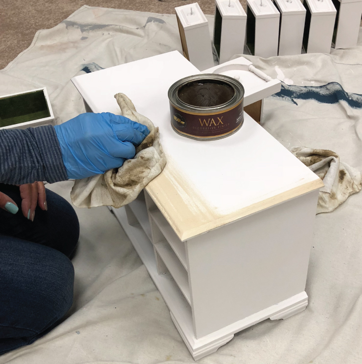 A person applying Behr decorative wax with a rag to the painted box.