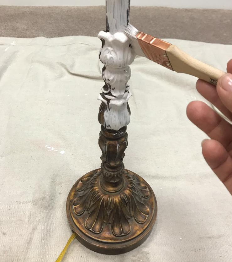 A lamp base getting a coat of fresh paint.