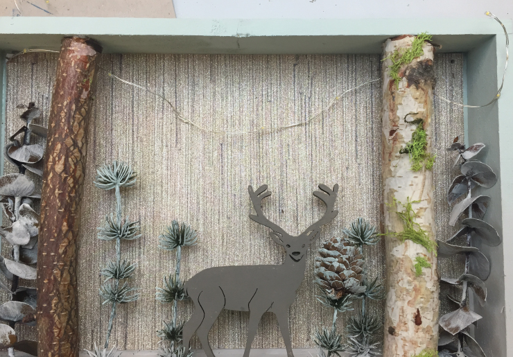 Finished shadow box with string lights, wooden deer and plants.