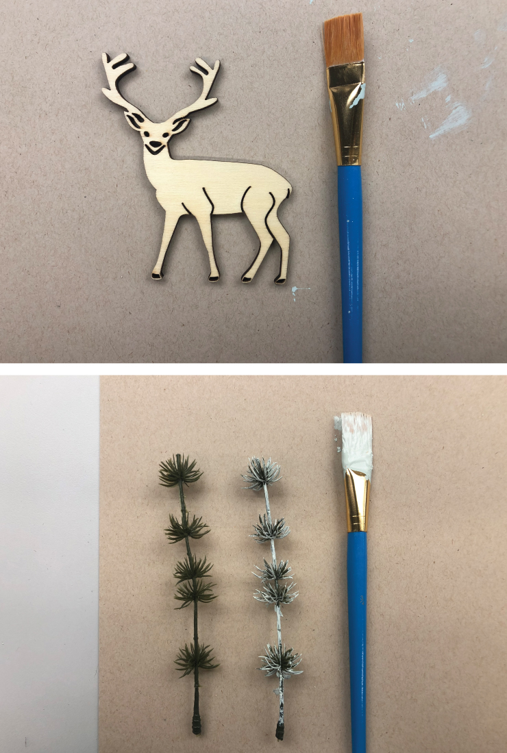 Material shot wooden deer, faux trees and a paint brush.