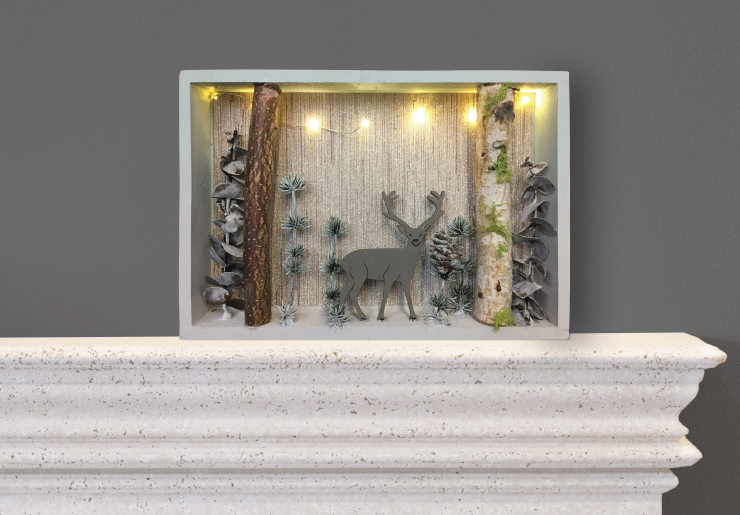 Finished shadow box with lights, twigs and a wooden deer.