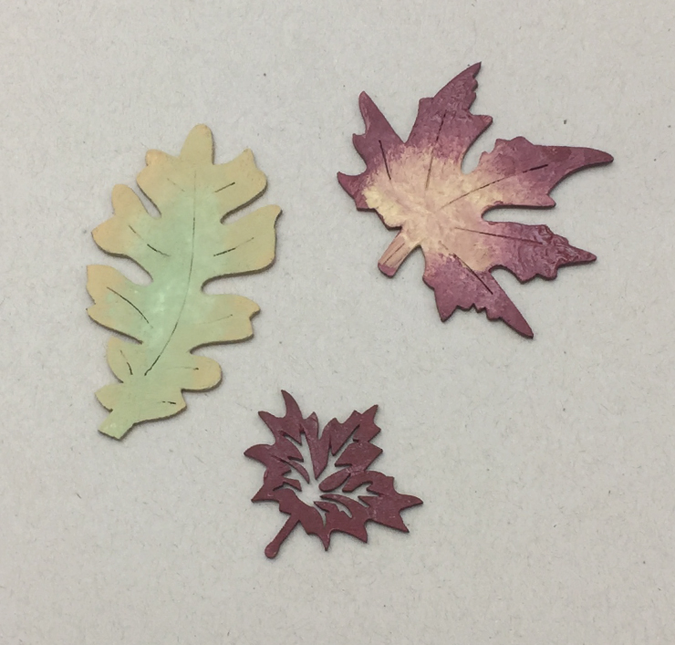 Three leaves painted. One is solid red leaf, the other two are painted sing two colors; yellow edges with green in center and then red on edges and yellow in center.