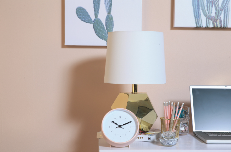 Detailed image of desk materials. On the desk we see a clock, a lamp, pencils and a computer. Behind the desk the wall is painted in Sand Dance S190-2