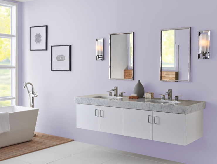 A large spa-like bathroom with wall mount sink furniture and a modern white ceramic tub. A wall size window allowing ample natural light into the room.  Walls painted in light purple color called Fanciful.