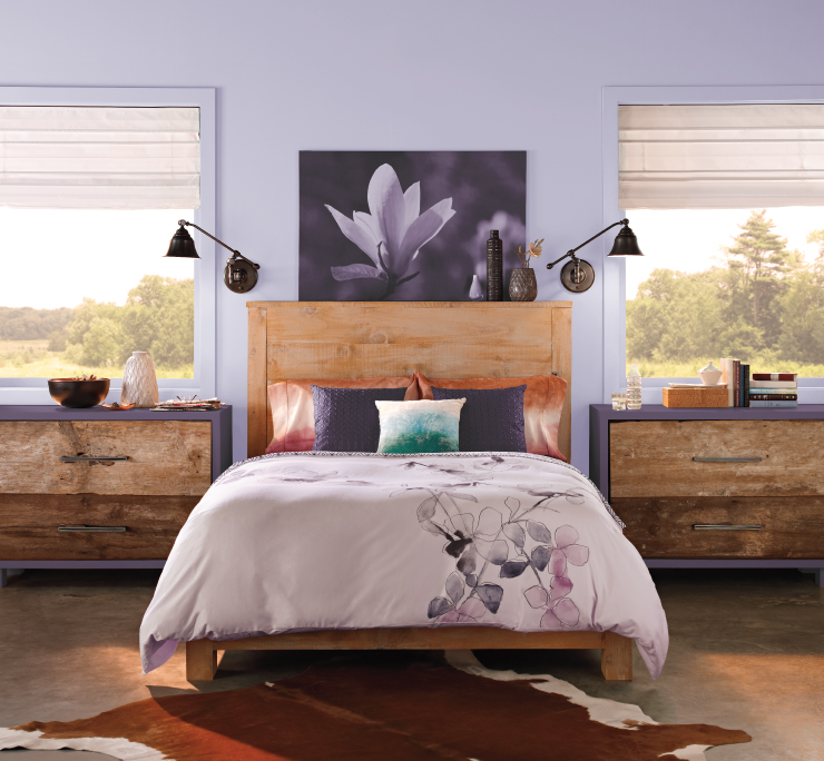 A modern rustic bedroom featuring cleaned lined and rough wood furniture.  Wall with two large windows, painted in a light purple color.