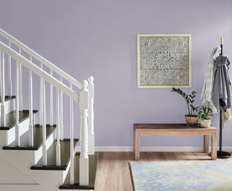 A light purple hallway and staircase area with minimal decorative elements. Hallway decorative elements include a sitting bench, coat rack. and wall artwork.