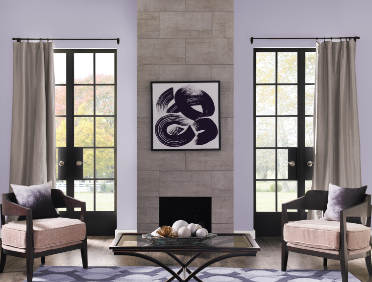 A classic living room with two large double metal and glass doors.  Tiled fireplace and walls painted in a light purple color called Fanciful.