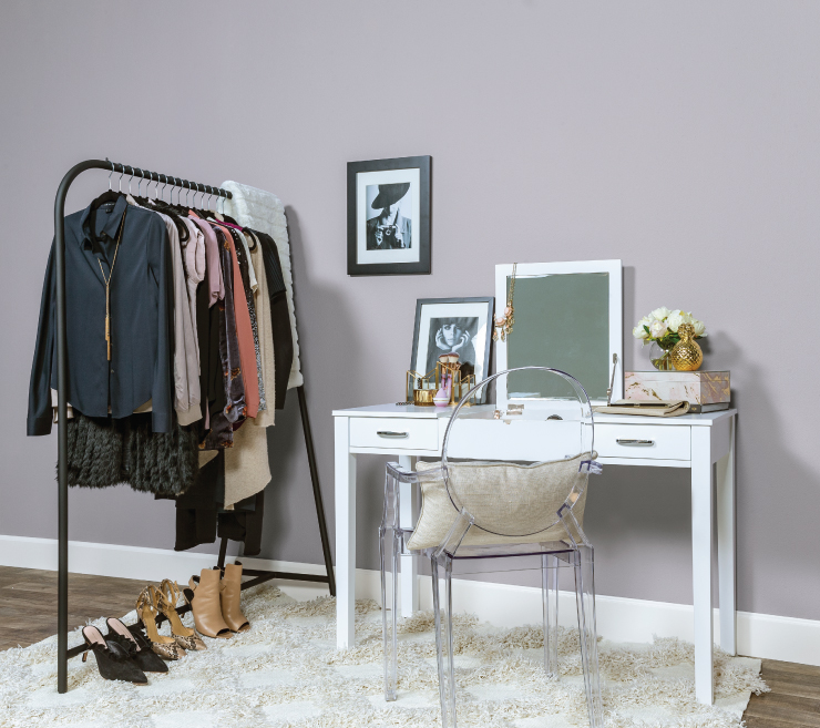 A dressing room area with a metal garnet rack and white vanity.  Wall painted in a dusty light purple called Standing Ovation.