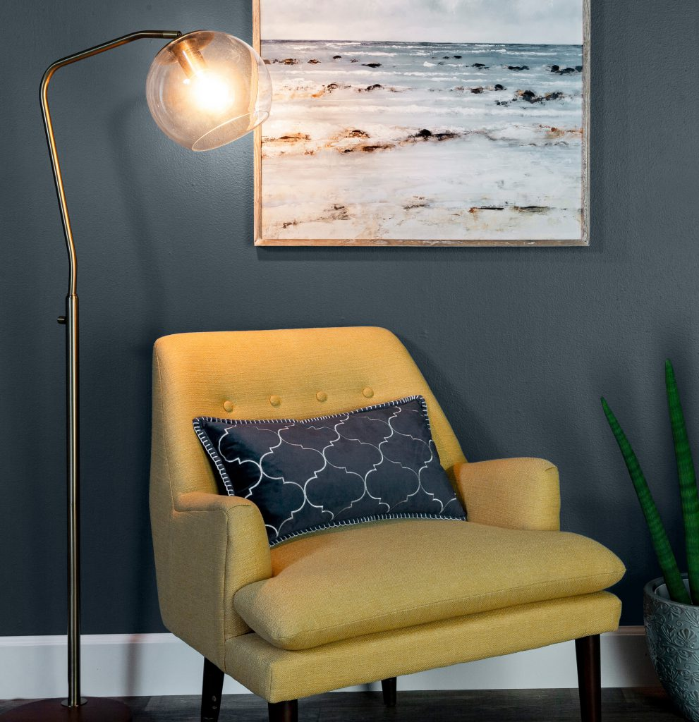 A sitting area with a yellow chair and a blue and white pillow. The wall behind the chair is painted in Blue Metal.