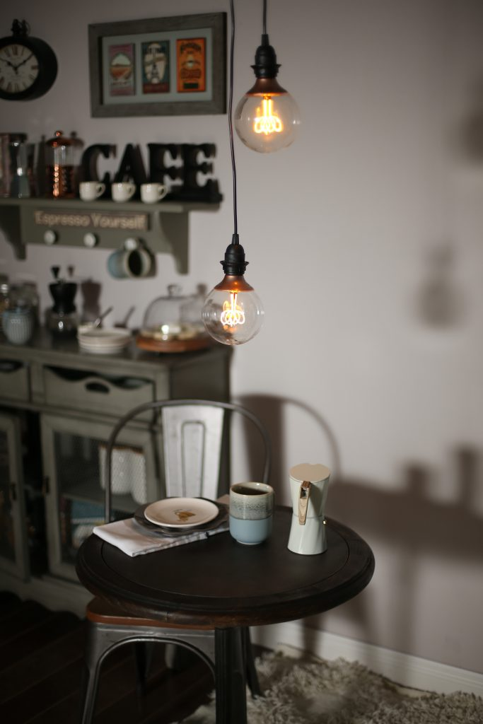 A close up of the small dining area with a small table and chair with hanging lights above. The table is set with a coffee mug, plate and pot of pressed coffee.