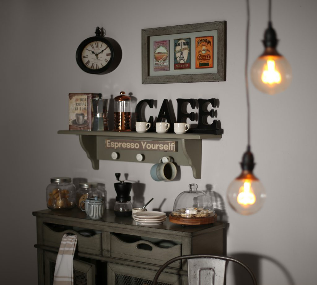 A close up of the buffet cabinet displaying coffee items; mugs, grinder, café sign. The hanging lights are blurred in the foreground of the image.