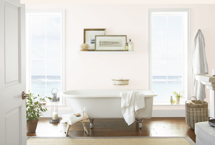 A ample pink bathroom with a lot natural light, a claw-foot tub and beautiful beach view.