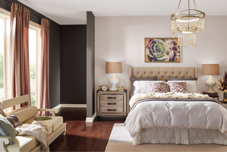 A classic pink and dark gray bedroom with a brick wall, two big windows and comfy furniture.