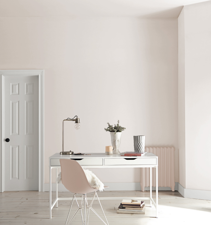 A modern, light pink and white home office with minimal decor.