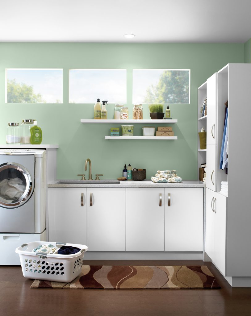 A contemporary light green laundry room with abundant natural light,  white cabinetry and washing machine.