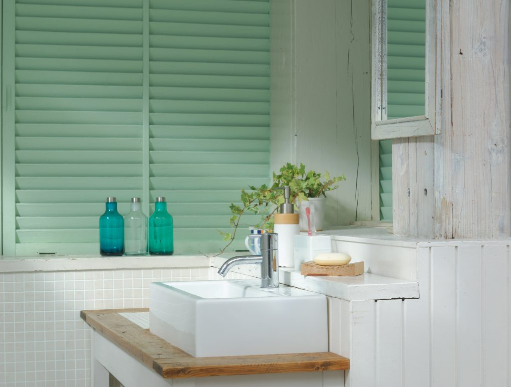 A small coastal bath with light green shutters.