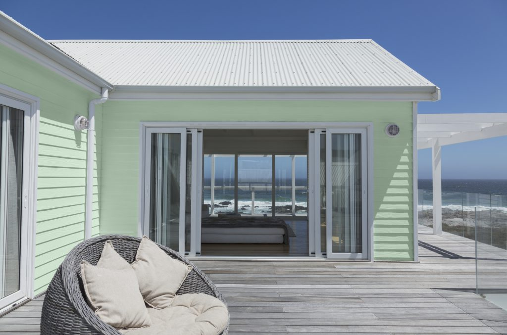 A beach house with  indoor and outdoor view.  House siding painted in light green color  and white roof.