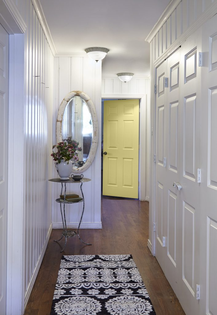 A hallway with white walls. The door at the end is painted in a bright yellow color, Spring Grass.