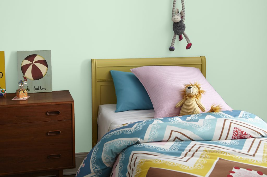 A child's bedroom showcasing a lgiht green wall, classic furniture and stuffed animal toys in bold colors