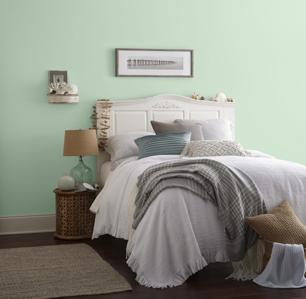 A peaceful coastal style bedroom with light green wall and comfy white bed.