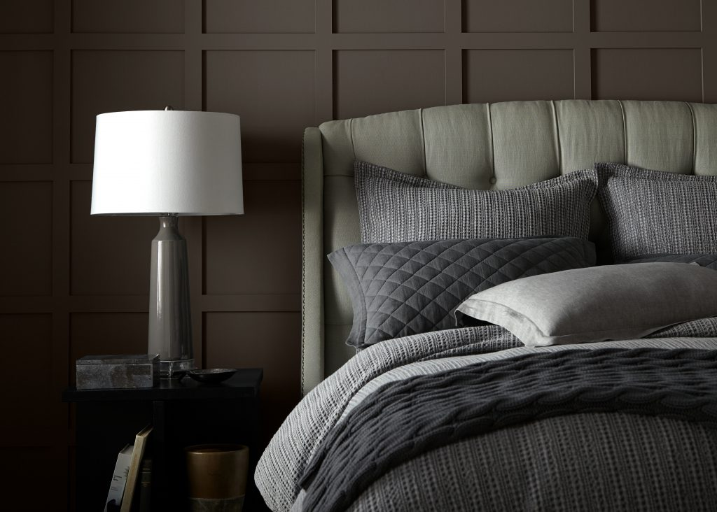A bedroom showcasing Kindling N200-6. The room consists of a grey bed and a grey and white lamp on a nightstand.