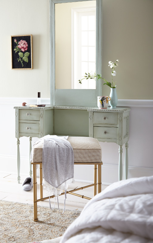 A make-up desk and mirror siting again a wall painted in a soft green paint color, Spring Valley