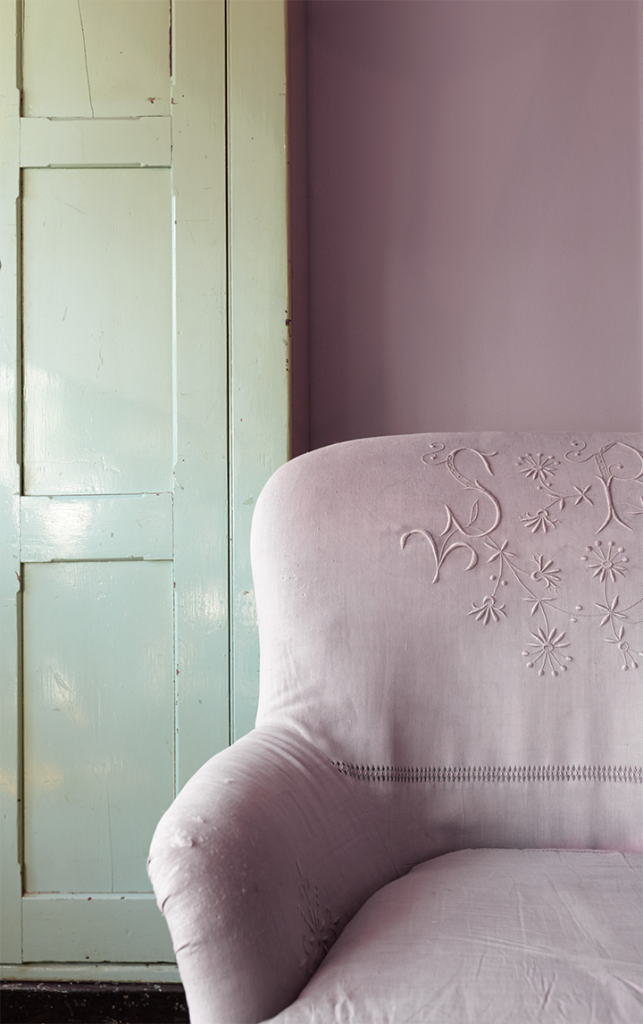 A  wall painted in Standing Ovation to compliment a green door and match the purple chair that is sitting in front of the wall.
